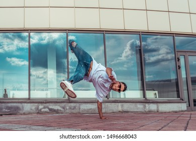 strong sporty man dancing break dance, stands one arm red-haired, young guy, motivation and lifestyle, summer city background of glass windows of building, jeans, sunglasses, white T-shirt