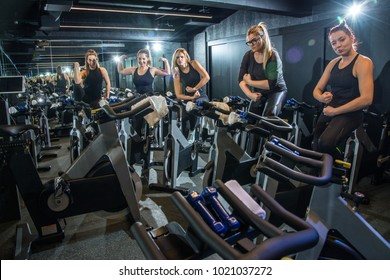 Strong sporty women showing and flexing their muscles while sitting on exercise bikes in gym.