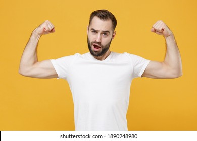 Strong sporty young bearded man 20s in white casual t-shirt posing isolated on yellow background studio portrait. People sincere emotions lifestyle concept. Mock up copy space. Showing biceps, muscles