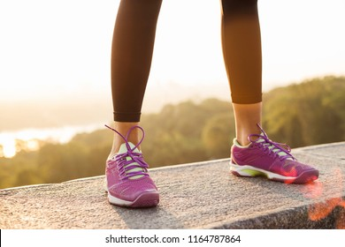 Strong standing. Close-up of young woman in cool sport sneakers standing against industrial city view  - Shutterstock ID 1164787864