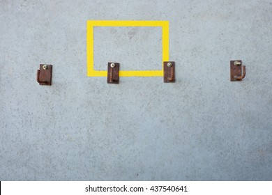 Strong steel wall hanger with yellow frame on concrete wall.
