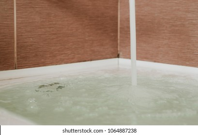 Strong stream of water pours into the tub. Water pours out. Tub overflows.