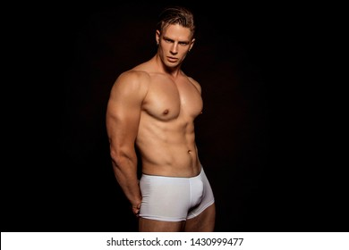Strong stripped muscle male model in white underwear on black isolated font background