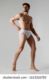 Strong stripped muscle male model in white underwear on gray isolated font background