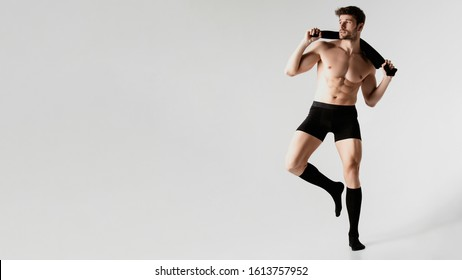 Strong stripped muscle male model in black underwear holding black t-shirt and black long socks on gray isolated font background
