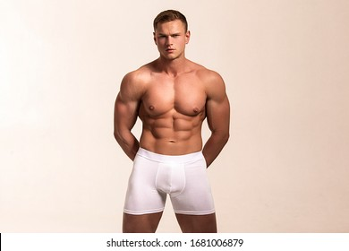 Strong stripped muscle male model in white underwear on white isolated font background