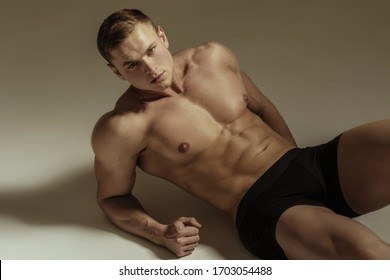 Strong stripped muscle male model in black underwear on gray isolated font background