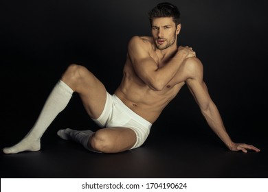 Strong stripped muscle male model in white underwear and white socks  on black isolated background