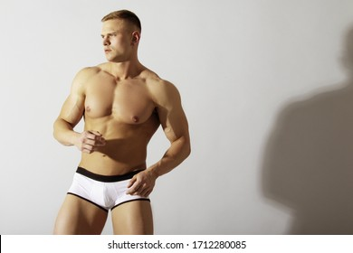 Strong stripped muscle male model in white underwear and white sneakers while having exercise on gray isolated font background