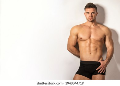 Strong stripped muscle male model in black boxers underwear on gray isolated font background