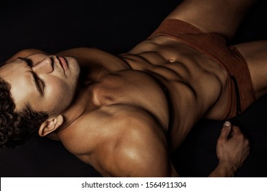 Strong stripped muscle swimmer male model in underwear and swimwear on black isolated font background