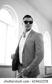Strong stylish successful man in a suit and glasses. Men's look. Black and white brutal man portrait. Businessman. Guy in suit and glasses posing on camera.