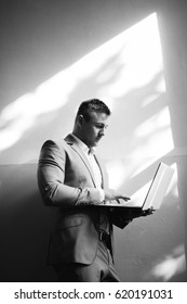 Strong stylish successful man in a suit and glasses. Men's look. Black and white brutal man portrait. Businessman. Guy in suit  posing on camera. Successful guy working on laptop. Hard light