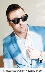 Strong stylish successful man in a suit and glasses. Men's look. Color brutal man portrait. Businessman. Guy in suit and glasses posing on camera.Stylish men's glasses and watches