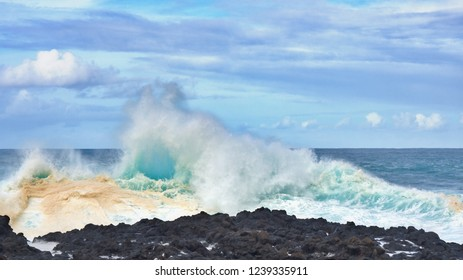 Strong surf on the Atlantic coast in the north of Tenerife. the spray shoots up and the waves roll over, from sea green to turquoise water color due to the high ozone content of the foamed water.