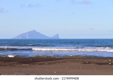 The strong surge and wave sprat at the coastline of Yilan County in Taiwan with the background of the landmark, Guishan Island.