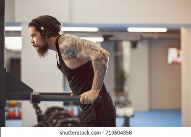 Strong tattooed in black unlabeled tank t-shirt male athlete shows calisthenic moves Holding dip position on parallel bars