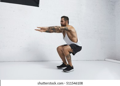 Strong tattooed in white unlabeled tank t-shirt male athlete shows calisthenic moves Squat hold plank exercise