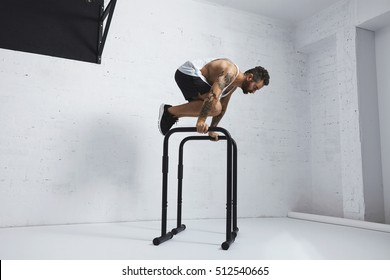 Strong tattooed in white unlabeled tank t-shirt male athlete shows calisthenic moves Holding tucked planche position on parallel bars