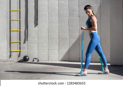 Strong toned woman using exercise equipment gear for weight loss and strength, copy space