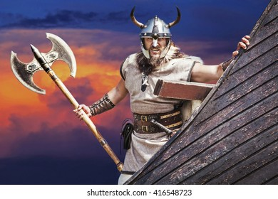 Strong Viking on his ship. Angry man holding historical axe weapon on ship looking at camera.
