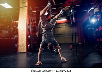 Strong vital sporty man standing on his hands in gym.