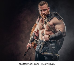 A strong warrior clad in light armor with a shield behind his back holds a sword and an axe