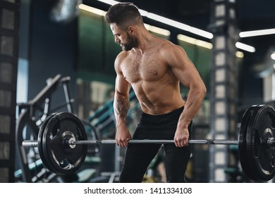 Strong weightlifter working out with heavy barbell in gym, free space