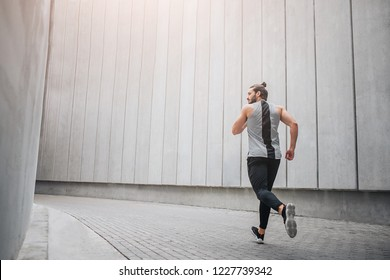 Strong and well-built runner jogging through concrete corridor. He jogging with all strenght and power. Young man looks to left. He is calm amd concentrated.