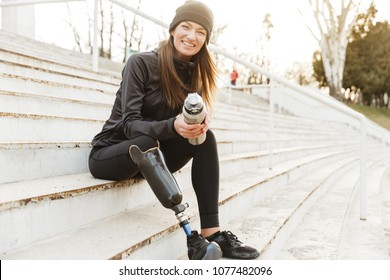 Strong willed handicapped woman in black tracksuit with prosthetic leg laughing while sitting at the street stairs with thermos cup in hands