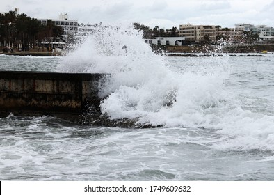 With the strong wind came huge waves that crash against the walls of the shore and shatter in all directions. Foamy sea. The power of the sea. The power of mother nature. Rainy weather. Paphos, Cyprus