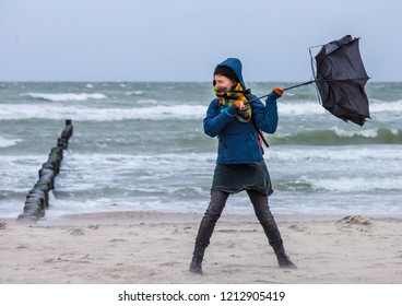 strong wind destroys a woman's umbrella during a beach walk