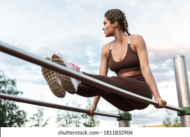 Strong woman athlete during calisthenics workout on a parallel bars