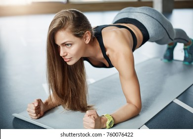 Strong woman body fitness coach making plank to strengthen her biceps triceps and abs. Female sport concept.