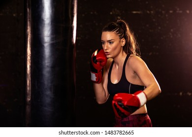 Strong woman with boxing gloves on hands exercise on gym