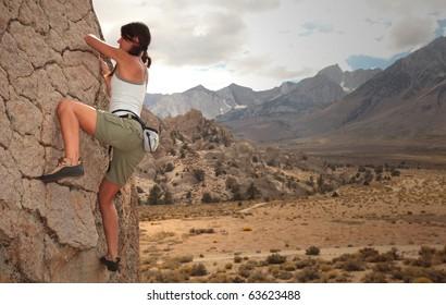 A strong woman climbs up a rock face.