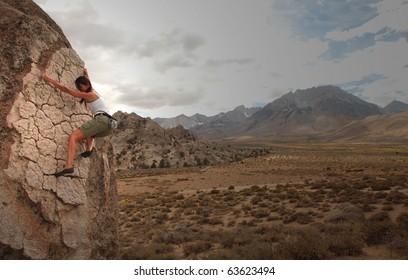 A strong woman climbs up a rock face in the Sierra Nevavda of California.