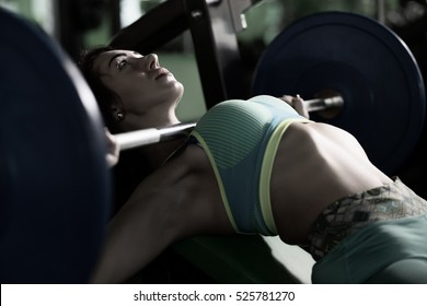 Strong woman doing bench press exercise in gym