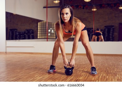 Strong woman doing kettlebell swing exercise at gym
