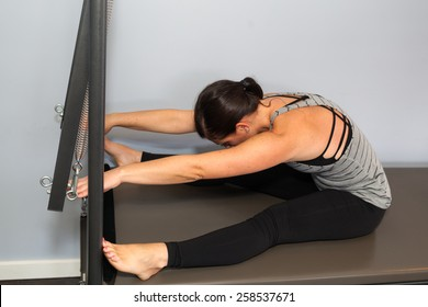 Strong woman doing Pilates on the Cadillac