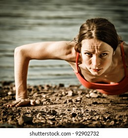 Strong woman doing push up at the beach