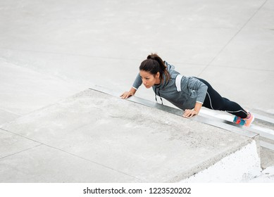 Strong woman doing push ups on urban stairs. Motivated female latin athlete training strength outside.