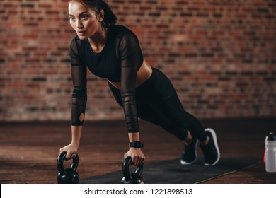 Strong woman doing push-ups on kettle bell in gym. Muscular female exercising in health club.