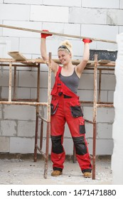 Strong woman in dungarees carrying big wooden plank board on her home construction site, building new home.