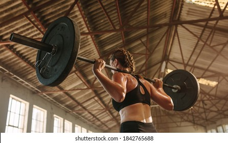 Strong woman exercising with barbell. Fit woman working out with heavy weights at cross training gym in factory shade.
