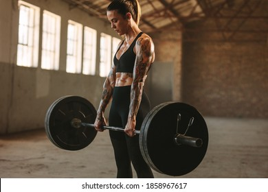 Strong woman exercising with heavy weights. Fit female doing deadlift workout with barbell in old warehouse.