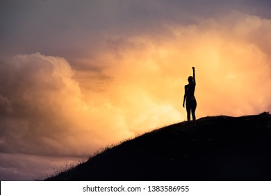 Strong woman with fist in the air standing on top a mountain. Triumph, victory and feeling determined.