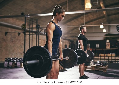 Strong woman and man holding heavy barbells in gym. Horizontal indoors shot