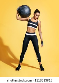 Strong woman with med ball on her shoulder. Photo of sporty latin woman in fashionable sportswear on yellow background. Strength and motivation.