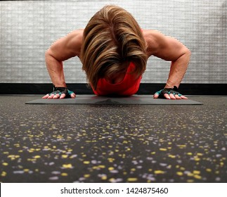 A strong woman over 50 exercising at the gym in the push up position.  There is an area for copy space below the woman on the gym floor area.